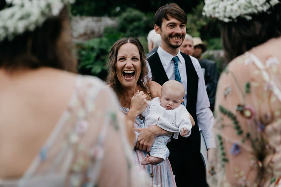 laughing wedding guest holding baby